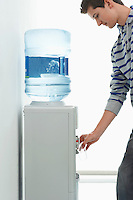 Man pouring drink from water cooler indoors