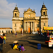 Street vendors in Parque Central (officially the Plaza de la Constitucion) in the center of Guatemala City, Guatemala, with the Catedral Metropolitana in the background.