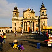 Street vendors in Parque Central (officially the Plaza de la Constitucion) in the center of Guatemala City, Guatemala, with the Catedral Metropolitana in the background.