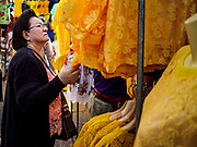 03 JULY 2018 - BANGKOK, THAILAND: A woman looks at yellow blouses at a shop in Bobae Market. The birthday of King Maha Vajiralongkorn Bodindradebayavarangkun, Rama X, is 28 July. The King, the only son of Thailand's late King Bhumibol Adulyadej, became the King of Thailand in 2016 after the death of his father. King Vajiralongkorn was born on 28 July 1952, a Monday. In Thai culture each day of the week has a color, and yellow is the color is associated with Monday, so people wear yellow for the month before his birthday to honor His Majesty.   PHOTO BY JACK KURTZ