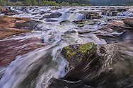 Sandstone Falls in West Virginia, the water breaks to and fro, weaving fantastic patterns with threads of white water into the fabric of the New River before crashing into the unforgiving rocks below.