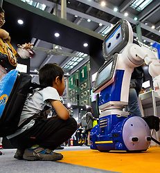 Young boy with robot at Shenzhen Hi Tech Fair 2016.