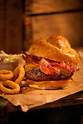 Bacon Cheddar Cheeseburger,onion rings,cold slaw sitting on brwon paper on top of old wooden crates,verticle