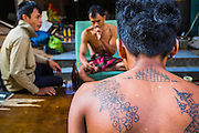 "11 DECEMBER 2012 - BANGKOK, THAILAND:  The tattooed back of a worker frames other workers who eat and drink in front of the empty building they live in while they demolish it at ""Washington Square"" a notorious entertainment district off Sukhumvit Soi 22 in Bangkok. Demolition workers on many projects in Thailand live on their job site tearing down the building and recycling what can recycled as they do so until the site is no longer inhabitable. They sleep on the floors in the buildings or sometimes in tents, cooking on gas or charcoal stoves working from morning till dark. Sometimes families live and work together, other times just men. Washington Square was one of Bangkok's oldest red light districts. It was closed early 2012 and is being torn down to make way for redevelopment.   PHOTO BY JACK KURTZ"