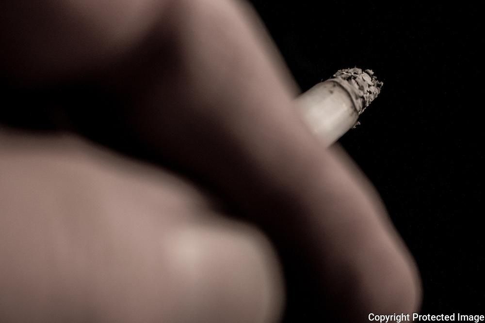 Close up of handing holding burning cigarette