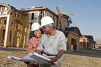 Middle-aged couple watching blueprints at construction site