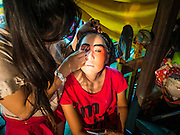 23 SEPTEMBER 2014 - BANGKOK, THAILAND:  A performer at the Chinese opera gets help putting on her makeup on the first day of the Vegetarian Festival at the Chit Sia Ma Chinese shrine in Bangkok. The Vegetarian Festival is celebrated throughout Thailand. It is the Thai version of the The Nine Emperor Gods Festival, a nine-day Taoist celebration beginning on the eve of 9th lunar month of the Chinese calendar. During a period of nine days, those who are participating in the festival dress all in white and abstain from eating meat, poultry, seafood, and dairy products. Vendors and proprietors of restaurants indicate that vegetarian food is for sale by putting a yellow flag out with Thai characters for meatless written on it in red.    PHOTO BY JACK KURTZ