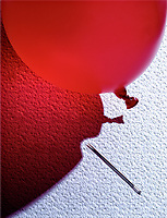An image of a balloon with a shadow avoiding a needle.