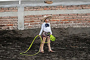Eight-year-old Juan Franco, from the legendary Franco family of Charro champions, prepares to rope a wild mare during a practice session in the Jalisco Highlands town of Capilla de Guadalupe, Mexico. The roping event is called Manganas a Pie or Roping on Foot and involves a charro on foot roping a wild mare by its front legs to cause it to fall and roll once. The wild mare is chased around the ring by three mounted charros.