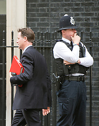 © Licensed to London News Pictures. 08/07/2014. Westminster, UK Deputy Prime Minister, Nick Clegg, walks past a police man as he leaves Downing Street today 8th July 2014 after the weekly cabinet meeting. Photo credit : Stephen Simpson/LNP