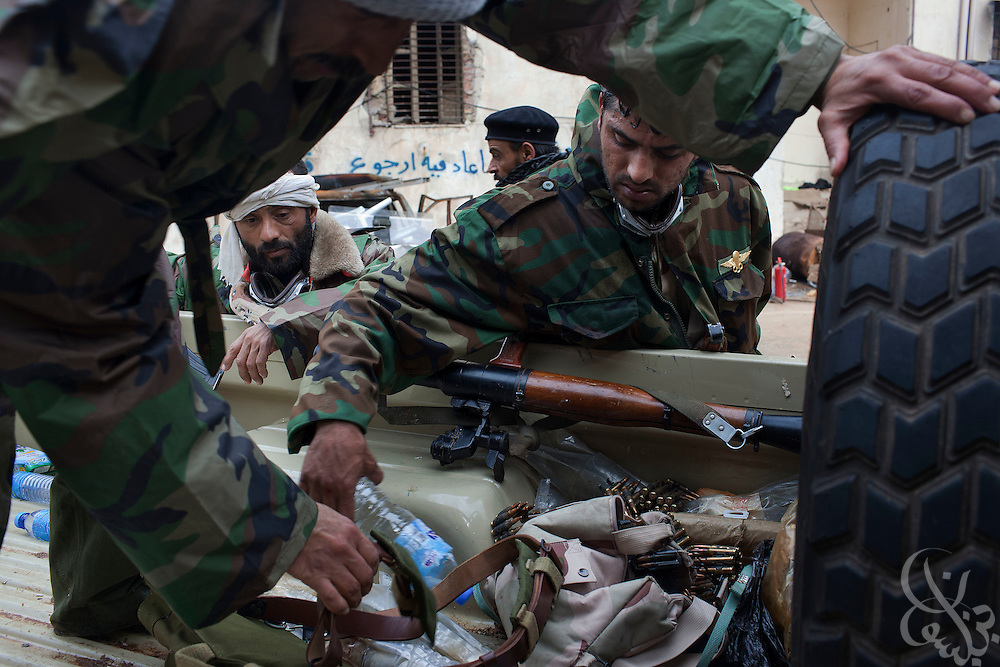 Libyan soldiers that have joined the revolution sort through reclaimed weapons that have been turned in by civilians February 25, 2011 at a temporary depot near the central square of Benghazi, Libya. Defected Several former soldiers also said that some 250 defected soldiers from a barracks near Benghazi had left for Tripoli to join the fight nearer to the capital, Tripoli..Slug: Libya.Credit: Scott Nelson for the New York Times