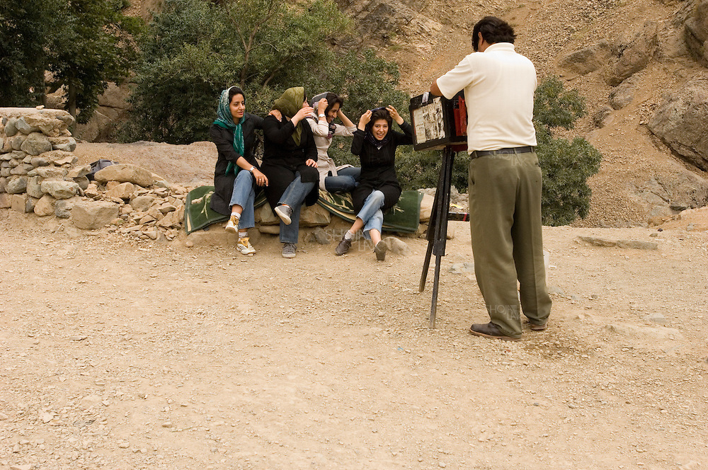 Tehran, Iran. August 23, 2007- Friends gather for a picture by a mobile photographer who uses an old fashion camera. This in the North Tehran mountains is famous for hiking.