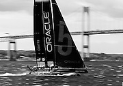 Newport, RI - Russell Coutts on Oracle 5 rips across Narragansett bay in front of the Newport Pell bridge.  The AC45 catamarans were racing during the America's cup world championships held in Newport.