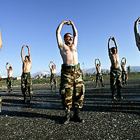 Iraqi Kurdish Peshmerga's, part of a brigade based around the Kurdish capital of Suleimaniya, stretch during a training exercise at the main Peshmerga base outside of the city of Suleimaniya, in northern Iraq. February 2005.