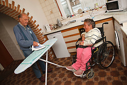Wheelchair user with Spina Bifida watching her father do ironing.