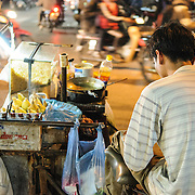 A vendor selling Vietnamese street food from a cart at night on a busy intersection in Hanoi's Old Quarter.