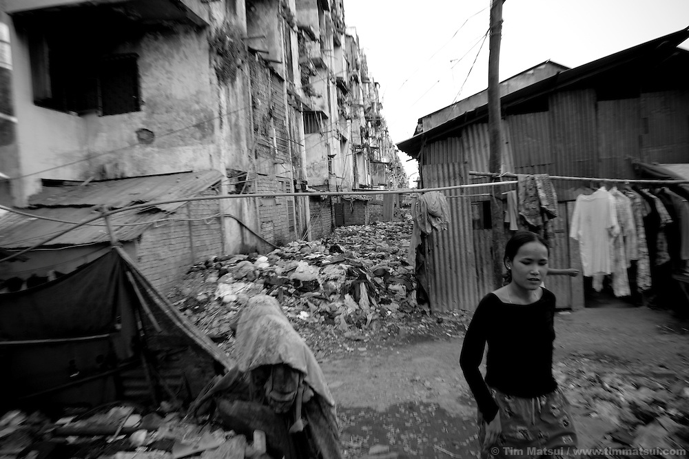 """Prostitute Srey Leat at home in a slum where the non governmental organization """"Acting for Women in Distressing Situations"""" (AFESIP), conducts outreach and provides services in Phnom Penh, Cambodia. The permanent structure, a decaying four story building known simply as 'The Building', was built in the 1960's as transitional housing and now hosts a shantytown where many of the city's poor live, including many prostitutes, and is believed to have the highest rate of HIV infection in the city. AFESIP hands out free condoms, instructs prostitutes on HIV prevention, and conducts outreach in case the prostitutes need medical services, choose to leave their profession, or can report on cases of sex trafficking. AFESIP offers housing, education, training, and counseling for women who are victims of sex trafficking, worked as prostitutes, or are escaping domestic violence. Founded by Somaly Mam, who herself was once a prostitute and victim of trafficking and domestic abuse, AFESIP has three facilities in Cambodia and works with other NGO's to provide long term care for the women."""