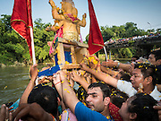 20 SEPTEMBER 2015 - SARIKA, NAKHON NAYOK, THAILAND:  People reach for a Ganesha deity before it's immersed in the river at the Ganesh festival at Shri Utthayan Ganesha Temple in Sarika, Nakhon Nayok. Ganesh Chaturthi, also known as Vinayaka Chaturthi, is a Hindu festival dedicated to Lord Ganesh. Ganesh is the patron of arts and sciences, the deity of intellect and wisdom -- identified by his elephant head. The holiday is celebrated for 10 days. Wat Utthaya Ganesh in Nakhon Nayok province, is a Buddhist temple that venerates Ganesh, who is popular with Thai Buddhists. The temple draws both Buddhists and Hindus and celebrates the Ganesh holiday a week ahead of most other places.   PHOTO BY JACK KURTZ