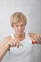 Man squeezing toothpaste on toothbrush in bathroom