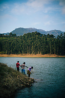 Munnar, India -- February 16, 2018: Men fish in a reservoir in Munnar.