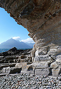 The classic view of violet-hued Gars-bheinn and the Cuillin from the incredible honeycomb textured Sandstone cliff at Port Elgol, Isle of Skye. <br />