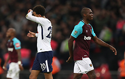 Tottenham Hotspur's Dele Alli (left) wipes his brow as he leaves the pitch at the end of the game