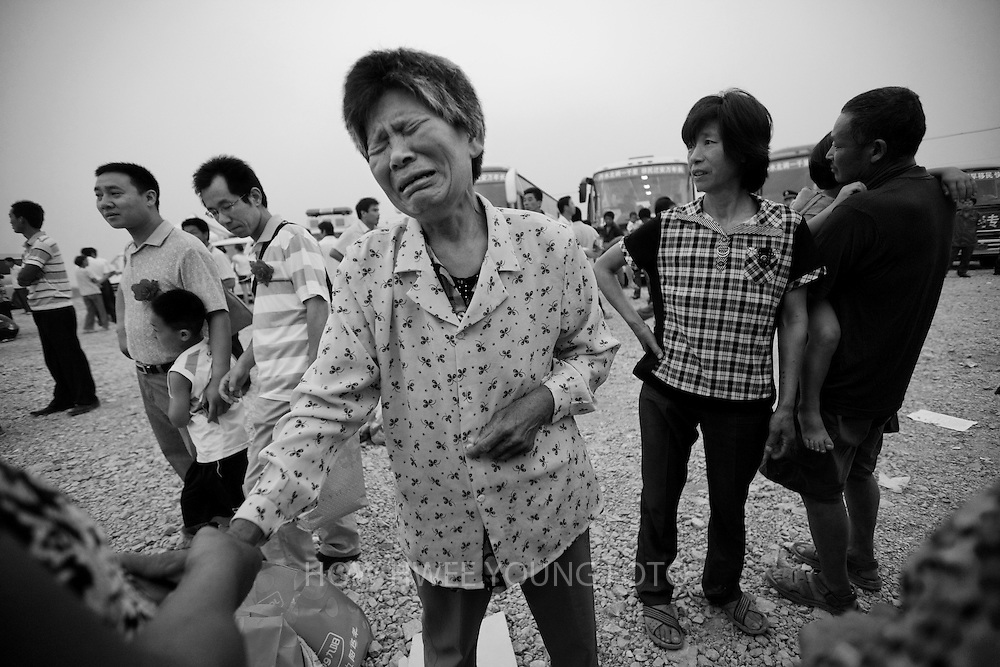 A migrant villager of Cangfang town cries as she bade farewell to her family before boarding a bus for relocation to neigbouring Hui county, more than 500 kilometers away, to make way for the colossal South-to-North Water Transfer project in Xichuan county of Henan Province in China on 29 June 2010. The South-to-North Water Transfer project, the largest known water diversion project, was conceived in 1952 to solve the country's chronic water shortages and involves creating three routes to channel 44.8 billion cu m of water from southern China to the northern areas. As part of the project's central route, affecting Henan and Hubei provinces, water from the Danjiangkou reservoir will be diverted to Beijing. The central route, which will raise the height of the Danjiangkou reservoir dam from 162 meters to 176.6 meters, requires the relocation of 330,000 people in Henan and Hubei provinces. Parts of Xichuan county, a remote, mountainous region inaccessible by railway and home to 162,000 migrants, the most anywhere, will be completely submerged by water from the Danjiangkou reservoir by 2014. The vast resettlement of affected residents in Xichuan county began in August 2009 and lasted till 2011.
