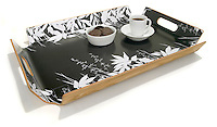 coffee and cookies on a black and white flowers serving tray with a wooden bottom