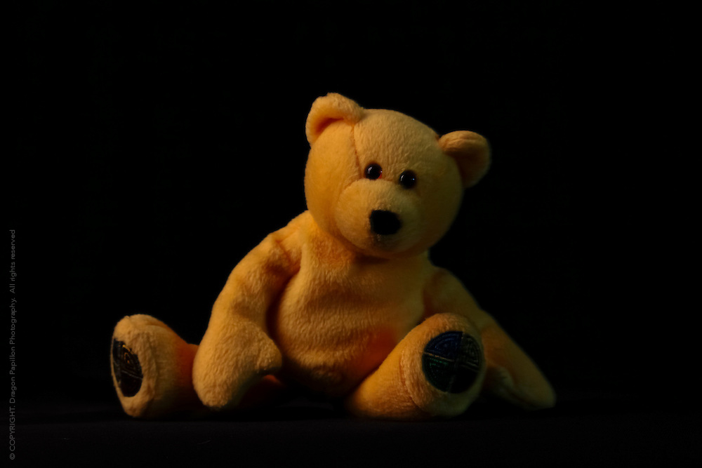 yellow teddy bear on black background