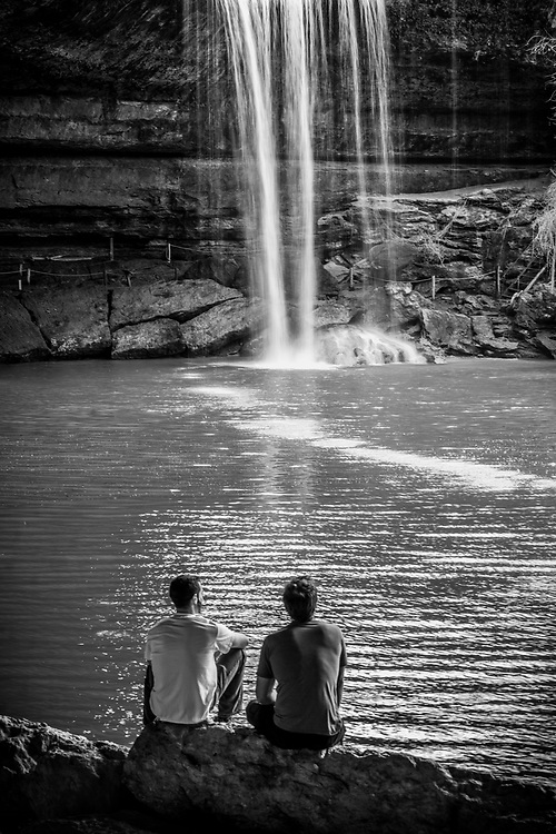 Visitors are enjoying the view of Hamilton Pool Preserve waterfall