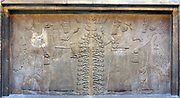 King Ashurnasirpal shown in a dual depiction at the Sacred Tree. The Sun God Shamash is also depicted.  Assyrian relief 865-860 BC from Nimrud