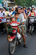 Phnom Penh, Cambodia. Evening rush hour seen from aboard a Tuk Tuk. Kids on motorbikes.