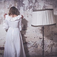 A young woman leaning against a wall beside her an old floor lamp