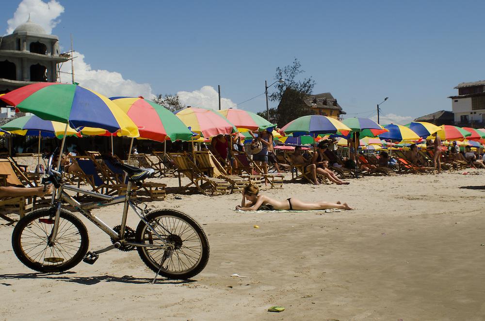 Rows of beach umbrellas tend to appear when the sun comes out in Montañita, Ecuador.