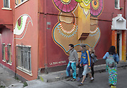 Pedestrians walk past a building covered in street art. Cerro Alegre, Valparaiso.