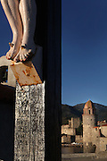 Detail of feet, statue of Christ Crucified, Chapelle St Vincent, 1642, Collioure, France with the Eglise Notre Dame des Anges and Chateau Royal in the background. Picture by Manuel Cohen.
