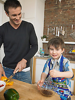 Father and son (3-4) preparing food in kitchen