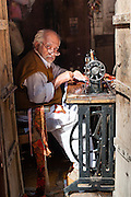 Old man sewing cloths with sewing machine (India)