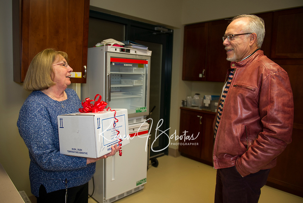 """RN Betty Quinlan-Sheldon talks with Dr. Wayne Domin in the """"milk room"""" during Wednesday evenings open house at LRGHealthcare Mothers' Milk Dispensary in Belmont.  (Karen Bobotas/for the Laconia Daily Sun)"""