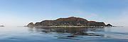 The island Runde, Nearby Fosnavåg, is located on the vestern part of Norway, and is famous for it's rich birdlife, and stunning nature | Panoramabilde av fugleøya Runde en tidlig morgen, mef flatt hav og refleksjon i sjøen.