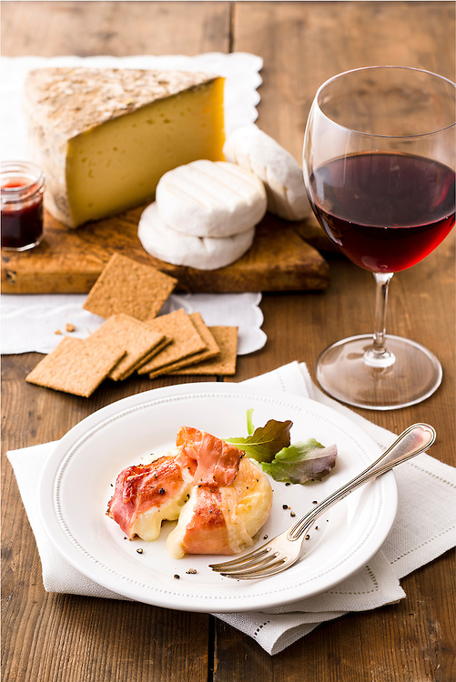 speck wrapped cooked tomino served with crackers and artisan cheese on a cutting board and one glass of red wine