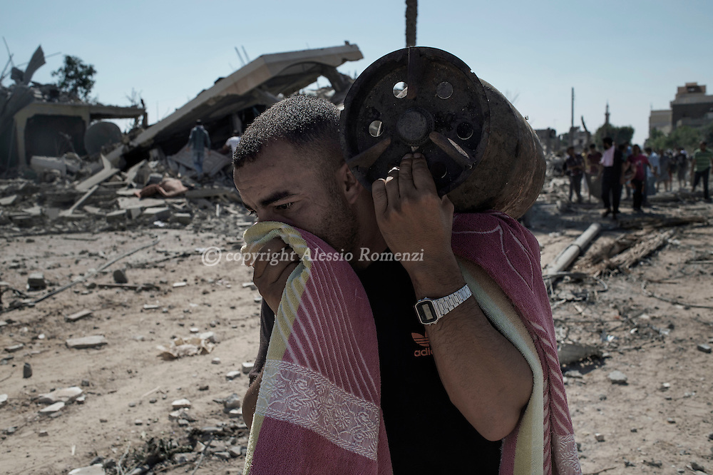Gaza Strip, Khuza'a: During a 72 hours shortly broken ceasefire a Palestinian man carries a gas bottle that he recovered from his house in Khuza'a on August 1, 2014. ALESSIO ROMENZI