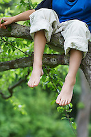 Young boy sitting on tree branch low section close up of feet