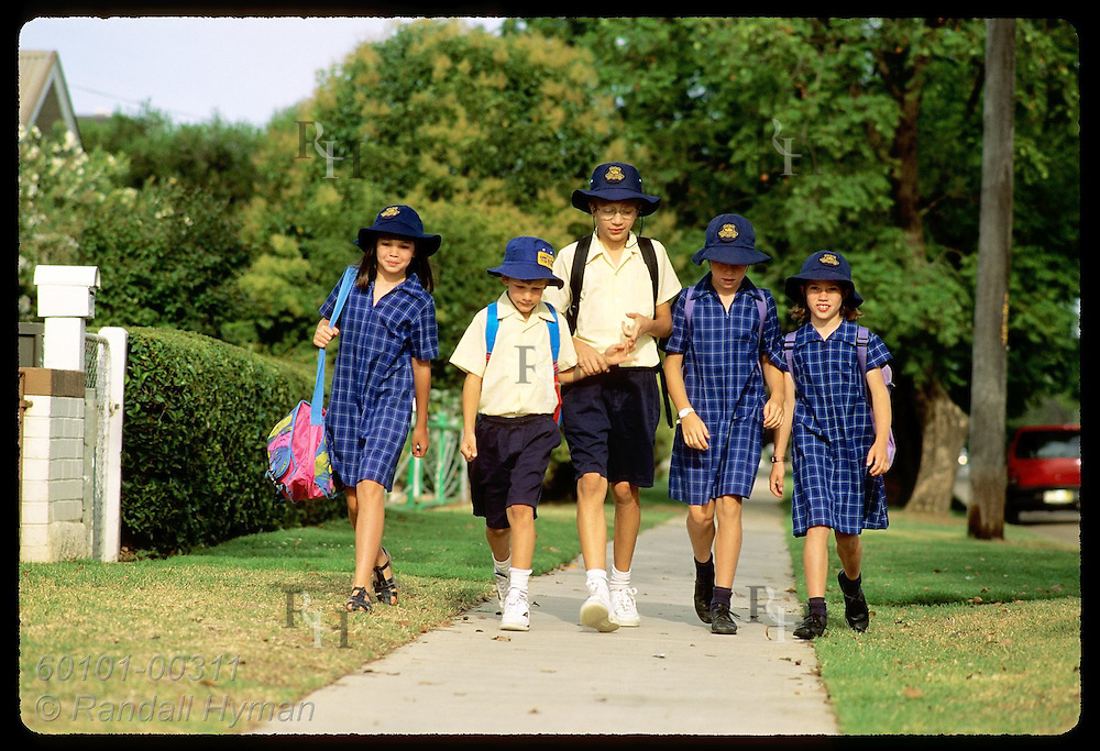 Girls and boys in uniforms walk to school together in early morn in town of Wagga Wagga, NSW. Australia