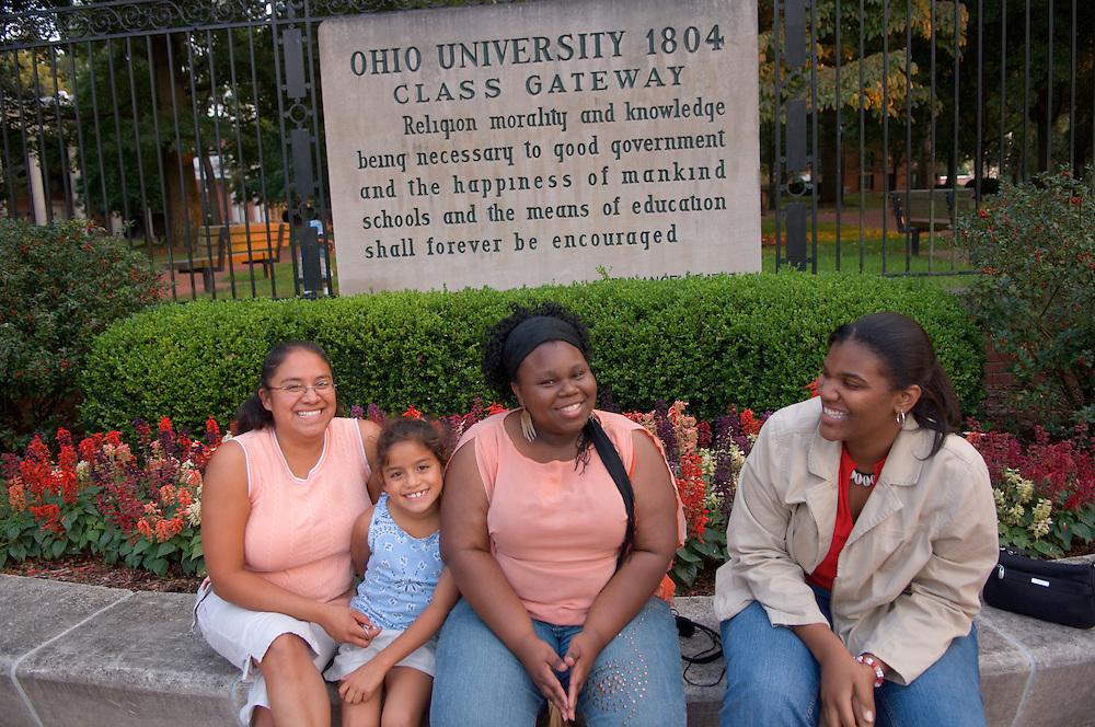 Reyna Mangrum(red shirt), Erial Ramsey(pink shirt middle dark skin), Liana Flores(glasses), Aurora Santiago-Flores(kid)