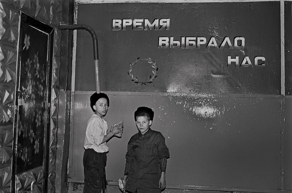 """Russian young prisoners work inside living room of the colony for prisoner's children in Siberian town Leninsk-Kuznetsky, Russia, 25 January 1999. On the wall reads """"The time chooses us""""."""
