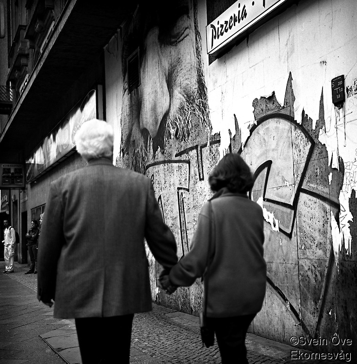 Et eldre ektepar går hånd i hånd forbi en grafittivegg i Berlin.<br /> <br /> Berlin street photography 2010. Berlin gatefoto 2010.<br /> Foto: Svein Ove Ekornesvåg