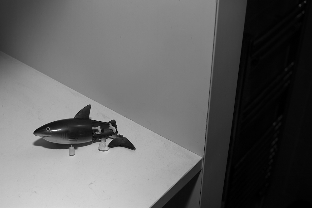 An injured shark toy lies broken on a shelf during bath time in Berkhamsted, England   Monday May 18, 2015. Children and mothers inhabit a strange place that until a few years ago I didn't know existed. Even as I child I was oblivious to it. Now my days are spent with costumed Storm Troopers patrolling my hallways. My evenings are filled with dinners and bath times and bedtime reading and tantrums and so much else. This is my new normal, and taking pictures makes me stop and look.