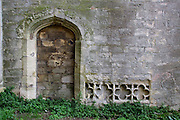 An infilled Gothic doorway with an adjacent irregular, presumably rebuilt wall incorporating quatrefoil stone carvings with vintage graffiti. Crowland Abbey, Lincolnshire.<br />