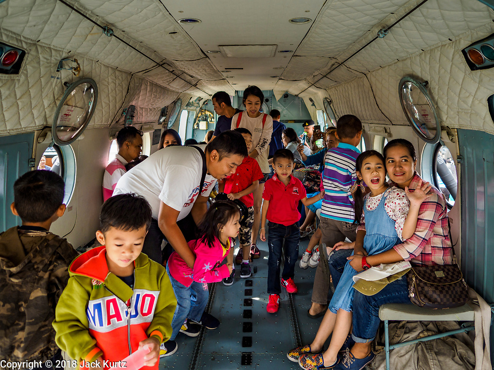 """13 JANUARY 2018 - BANGKOK, THAILAND: Thai children and their parents in a Thai Army Mi-17 """"Hip"""" (NATO designation) helicopter during Children's Day activities at the Royal Thai Army's King's Guard 2nd Cavalry Camp in central Bangkok. Children's Day is called """"Wan Dek"""" in Thai. Many government offices and military bases hold special activities for children as do shopping malls.       PHOTO BY JACK KURTZ"""
